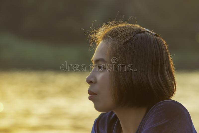 Portret van Aziatische vrouwenzitting door de rivier en het weerspiegelde lichte goud in water stock afbeelding
