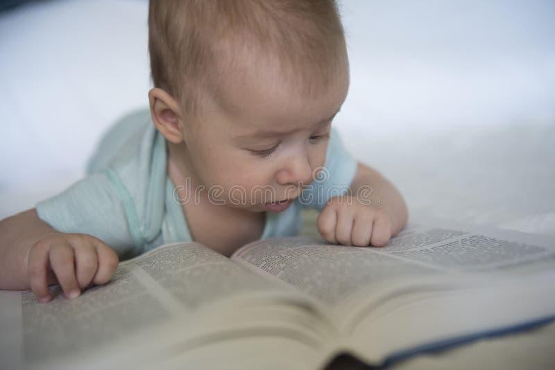 Portret van babymeisje het proberen om boek te lezen royalty-vrije stock afbeelding