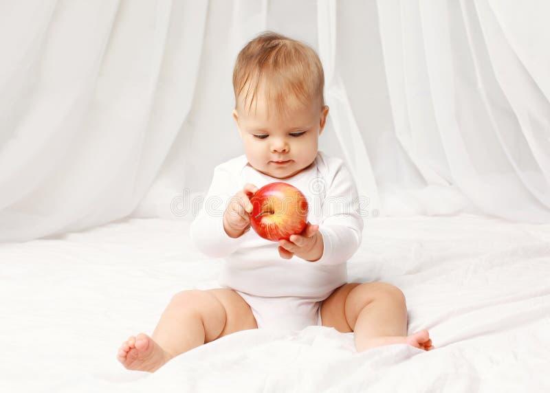 Portret van babyzitting met rode appel op het bed stock foto's