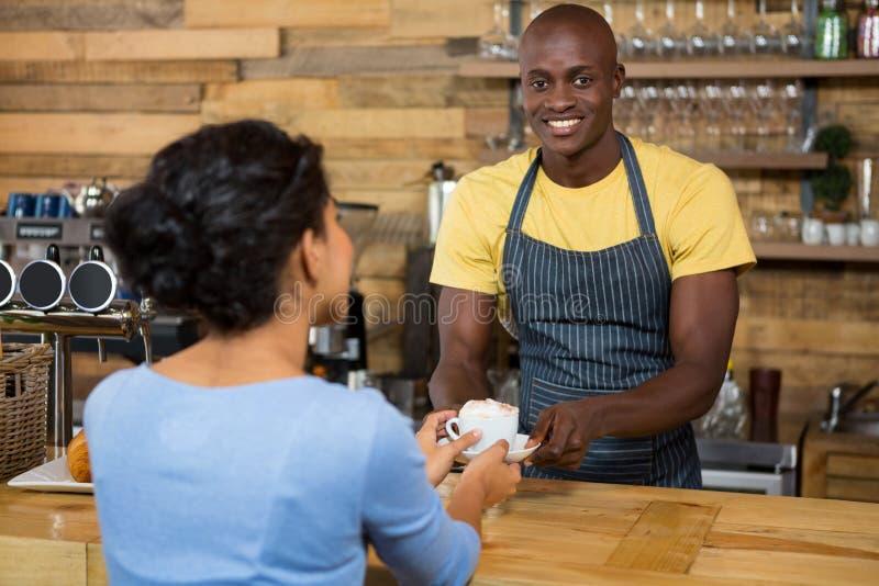 Portret van barista dienende koffie aan klant in koffie royalty-vrije stock afbeeldingen