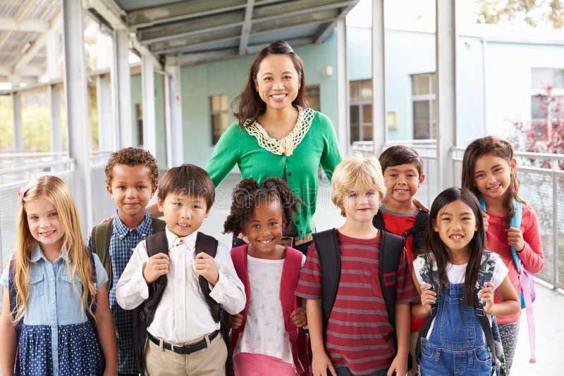 Portret van basisschooljonge geitjes en leraar in gang stock fotografie