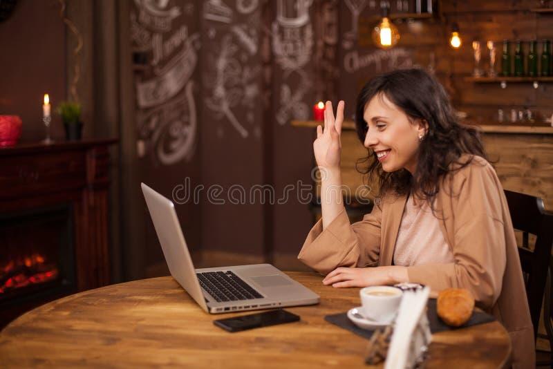Portret van beautiul het moderne ondernemer golven bij de laptop camera in een telefonische vergadering stock fotografie