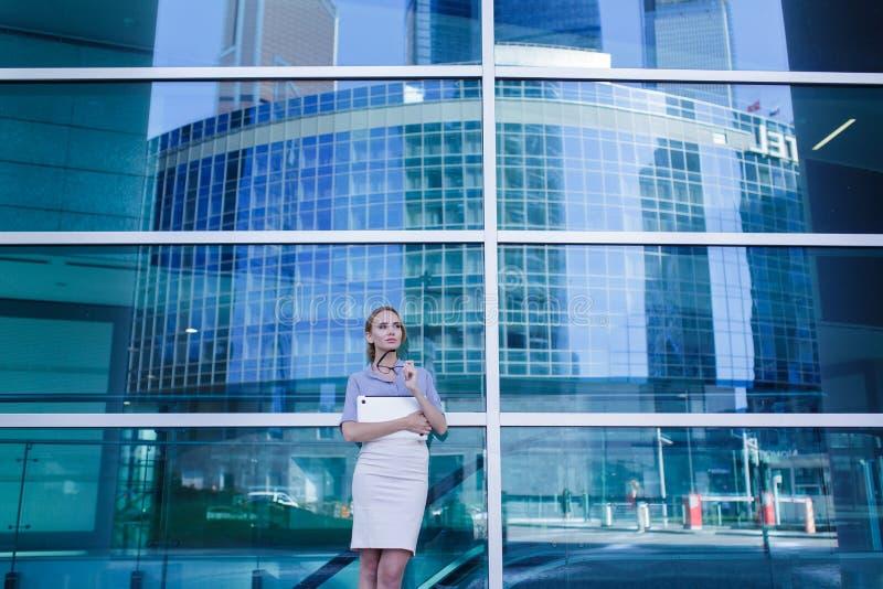 Portret van bedrijfsvrouw met laptop in haar handen die zich naast het bureaugebouw bevinden royalty-vrije stock foto