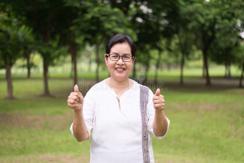 Portret van bejaarde Aziatische vrouw die duim tonen bij openbaar park, Gelukkig en glazen dragen die, het Positieve houding denk royalty-vrije stock afbeeldingen