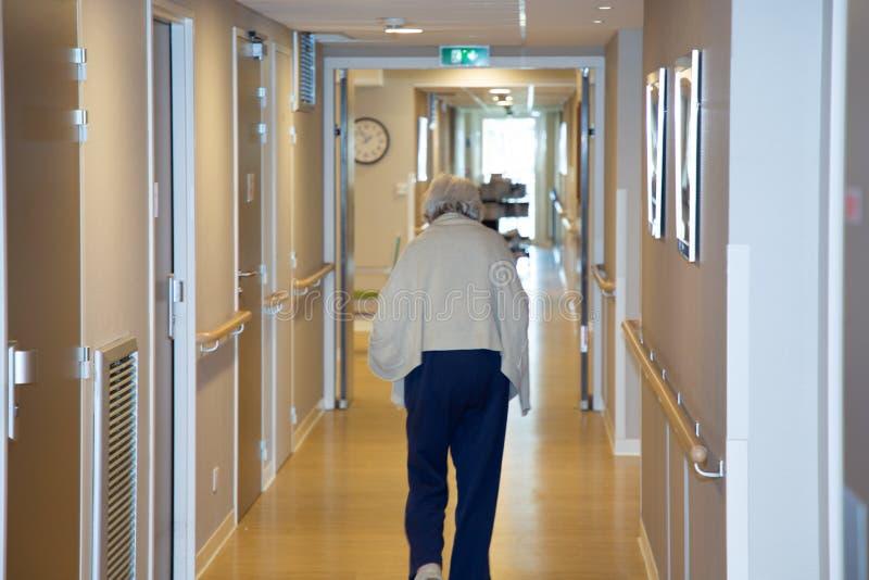 Portret van bejaarde het lopen onderaan gang op de achtergrond van het pensioneringshuis stock foto