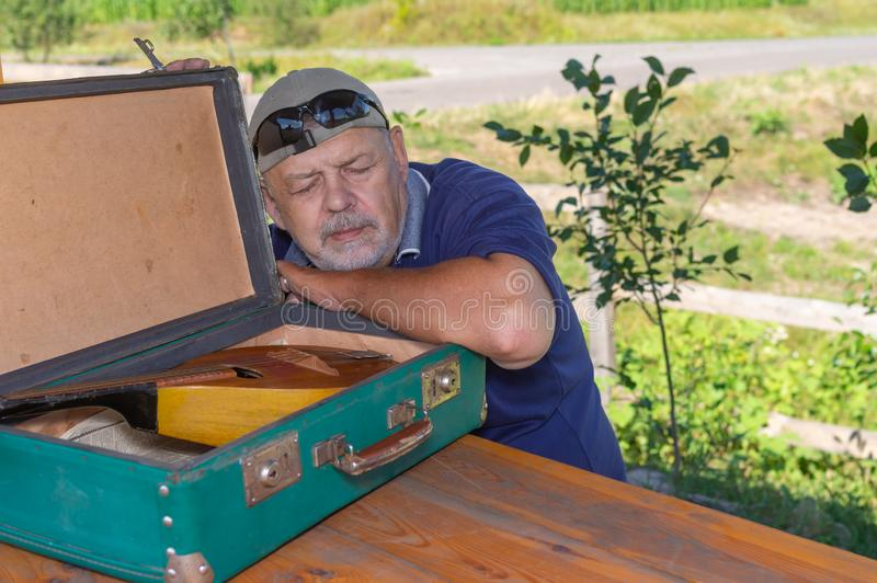 Portret van bejaarde Kaukasische mensenslaap dichtbij open koffer met mandoline royalty-vrije stock fotografie