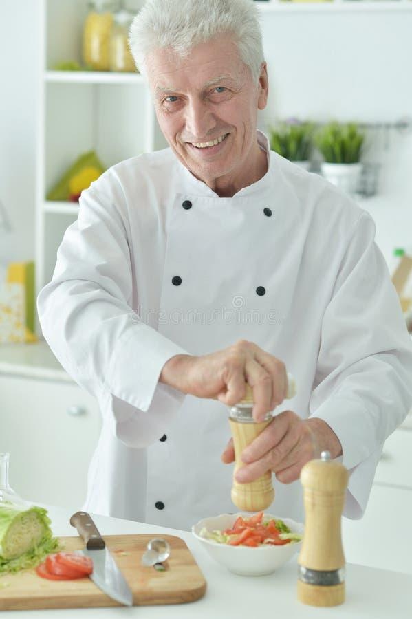 Portret van bejaarde mannelijke chef-kok die salade kruiden stock foto