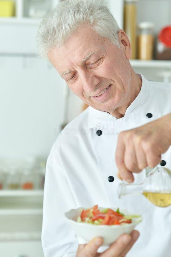 Portret van bejaarde mannelijke chef-kok gietende olie in salade royalty-vrije stock fotografie