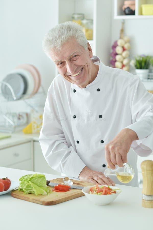 Portret van bejaarde mannelijke chef-kok gietende olie in salade royalty-vrije stock foto's