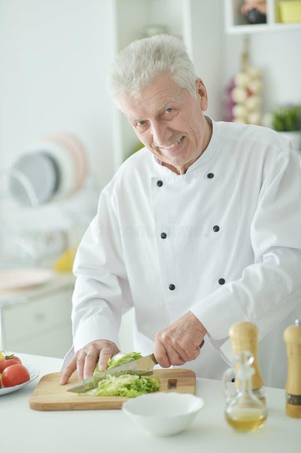 Portret van bejaarde mannelijke chef-kok scherpe kool bij keuken stock fotografie