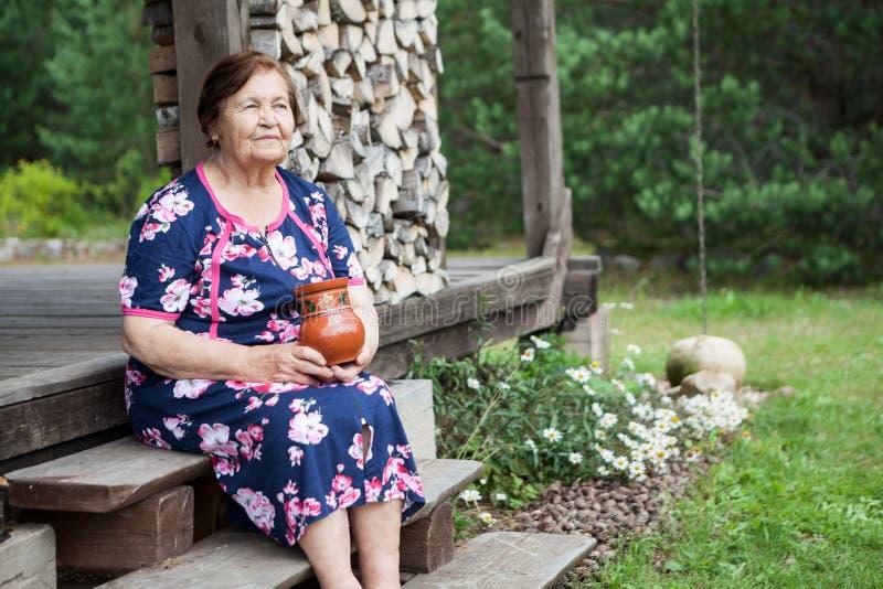 Portret van bejaarde met melkkruik in handen, buitenhuis houten veranda met houten-stapel, copyspace stock afbeelding