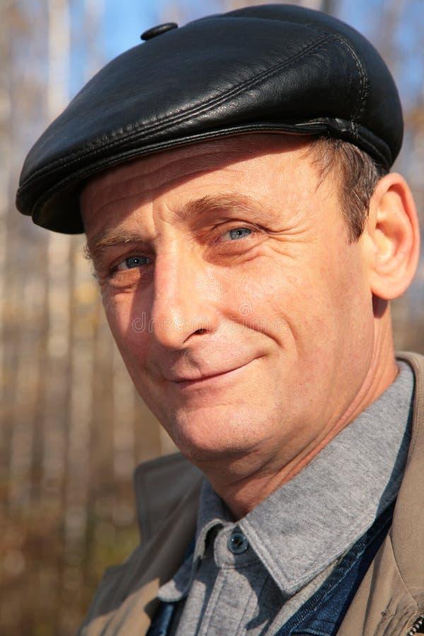 Portret van bejaarde in zwarte hoed in hout stock fotografie