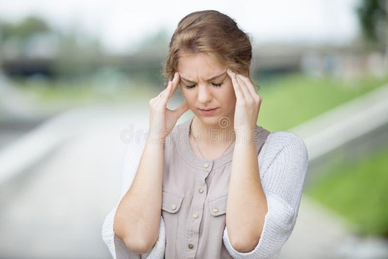 Portret van beklemtoonde vrouw met hoofdpijn in openlucht royalty-vrije stock foto's
