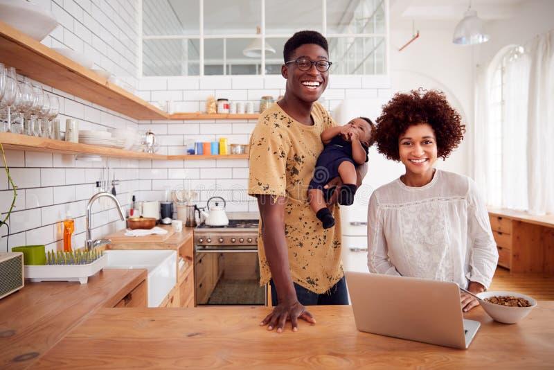 Portret van Bezige Familie in Keuken bij Ontbijt met de Zoon van Vadercaring for baby stock fotografie