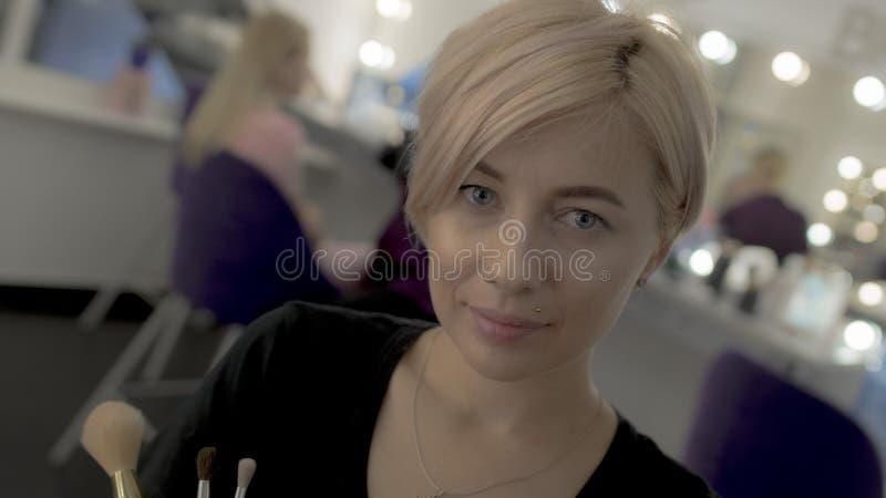 Portret van blauw-eyed blonde met kort kapsel die camera bekijken stock fotografie