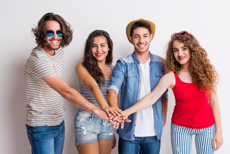 Portret van blije jonge groep vrienden die hun handen in een studio samenbrengen stock afbeeldingen
