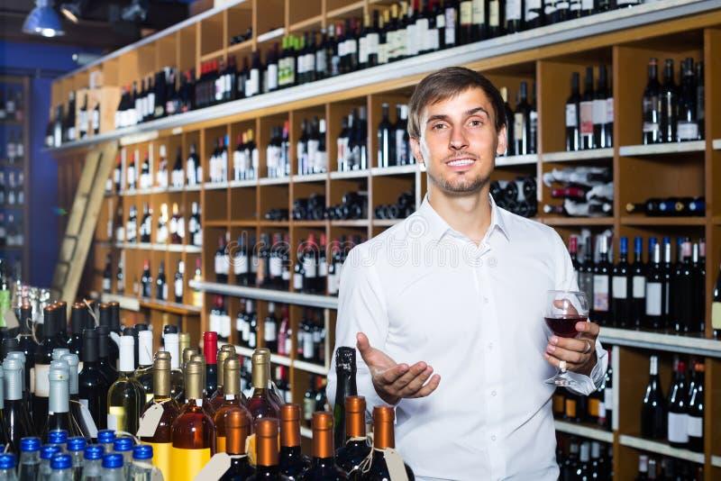 Portret van blije mannelijke klanten proevende wijn alvorens het te kopen stock foto