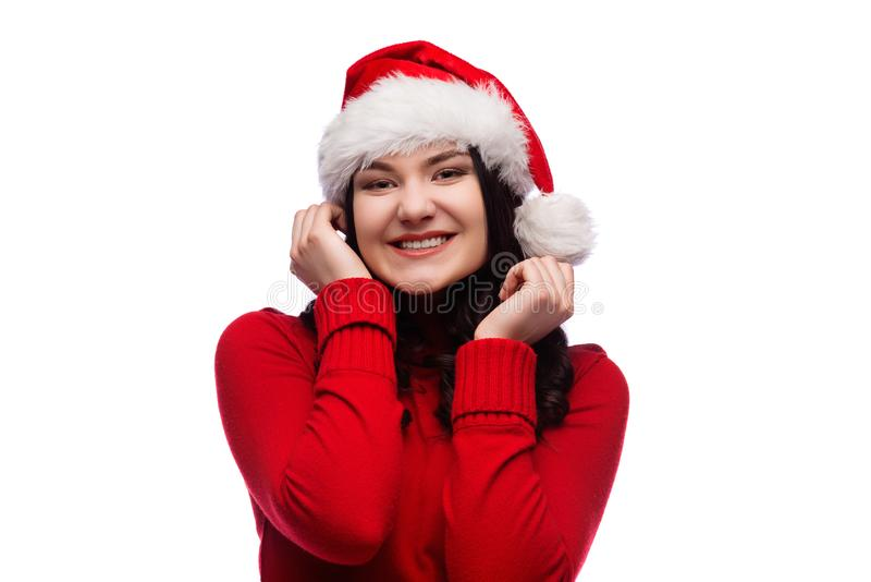 Portret van blije vrouw die santahoed in rode sweater dragen, ruim en palmen glimlachen houden dichtbij geïsoleerde wangen, royalty-vrije stock foto's