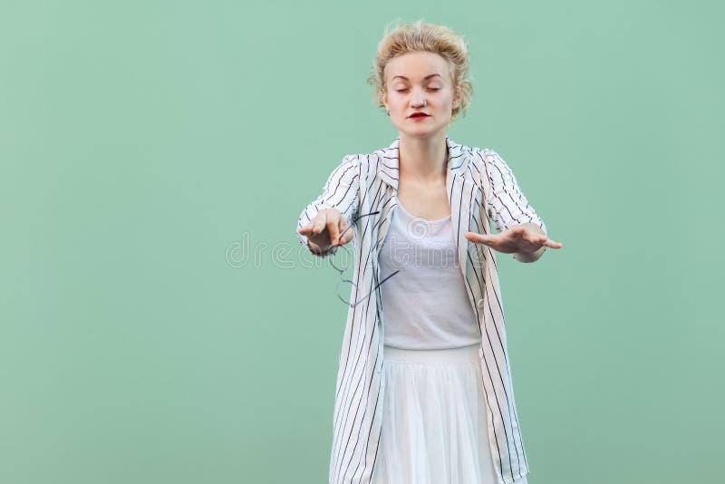 Portret van blinde jonge blondevrouw in wit overhemd, rok, en gestreepte blouse die, zich met gesloten ogen bevinden en het probe royalty-vrije stock afbeeldingen