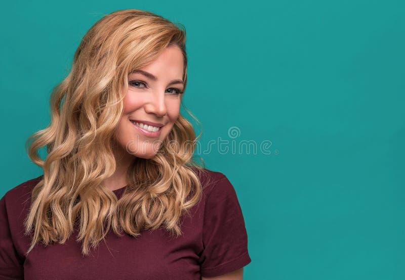 Portret van blonde glimlachende vrouw op een blauwe achtergrond stock foto