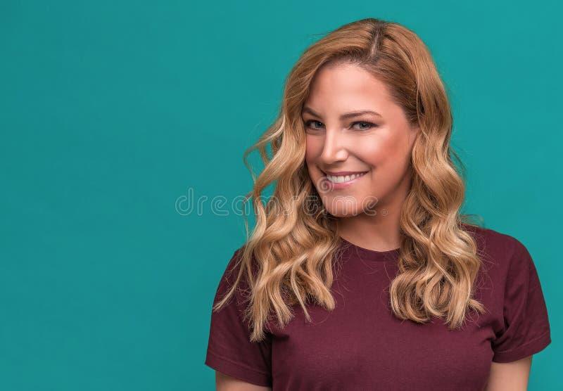 Portret van blonde glimlachende vrouw op een blauwe achtergrond stock afbeeldingen