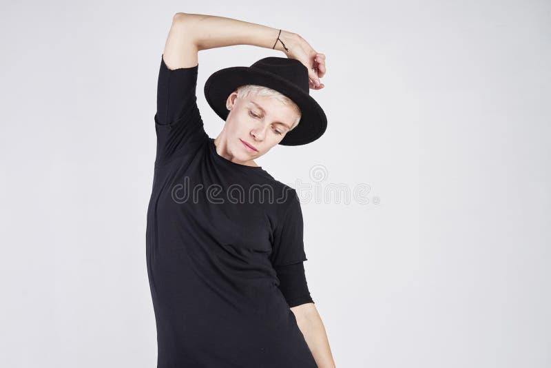 Portret van blonde Kaukasische vrouw die zwarte kleren en hoed het stellen op witte achtergrond dragen royalty-vrije stock afbeelding