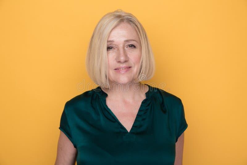 Portret van blonde volwassen die vrouw in een studio op een gele achtergrond wordt geïsoleerd stock foto