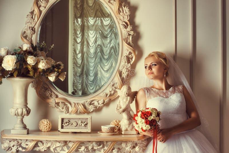 Portret van blondebruid dichtbij de spiegel stock fotografie