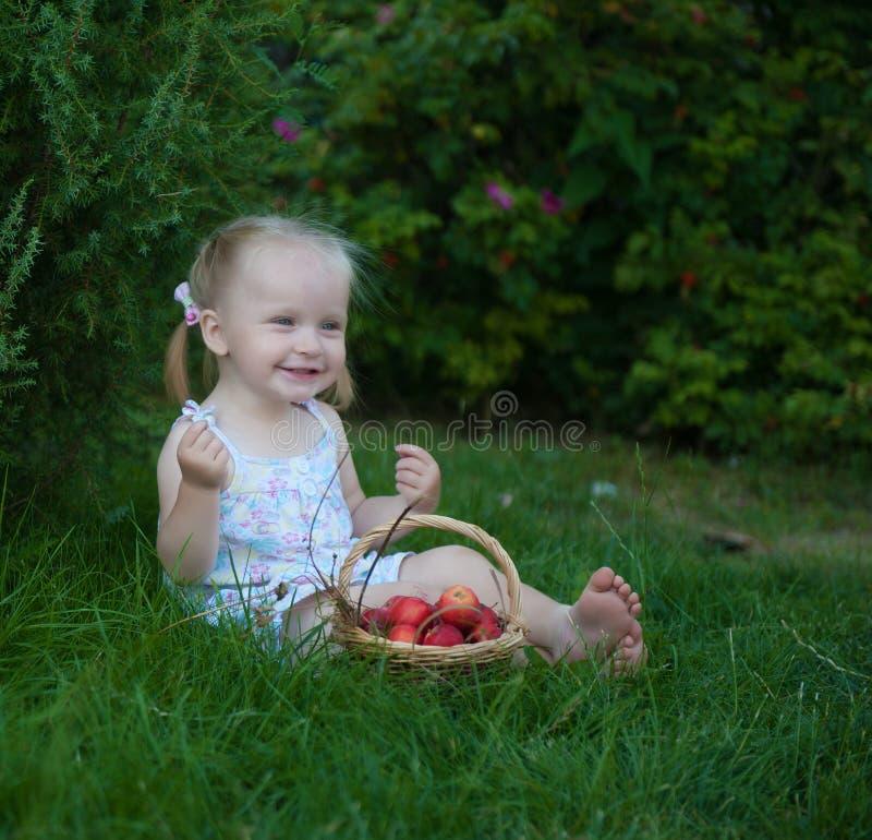 Portret van blondemeisje met rode appelen stock fotografie