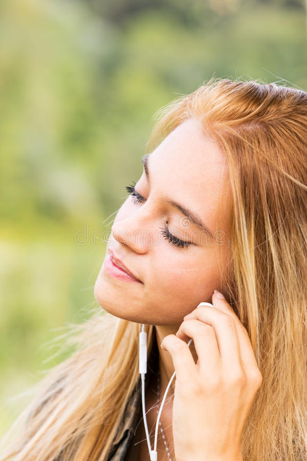 Portret van blondemeisje in oortelefoons stock foto