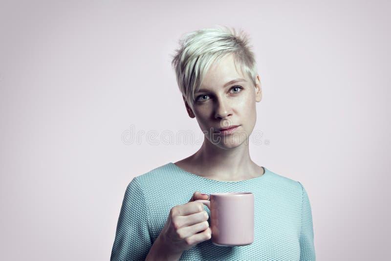 Portret van blondevrouw met kop van water, korte haar heldere achtergrond als achtergrond royalty-vrije stock foto's