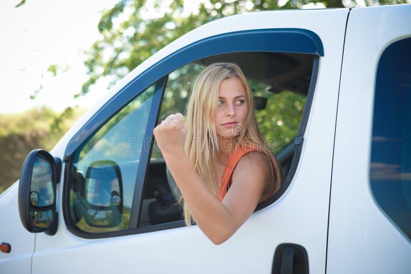 Portret van boos blond meisje in het witte auto tonen stock foto's