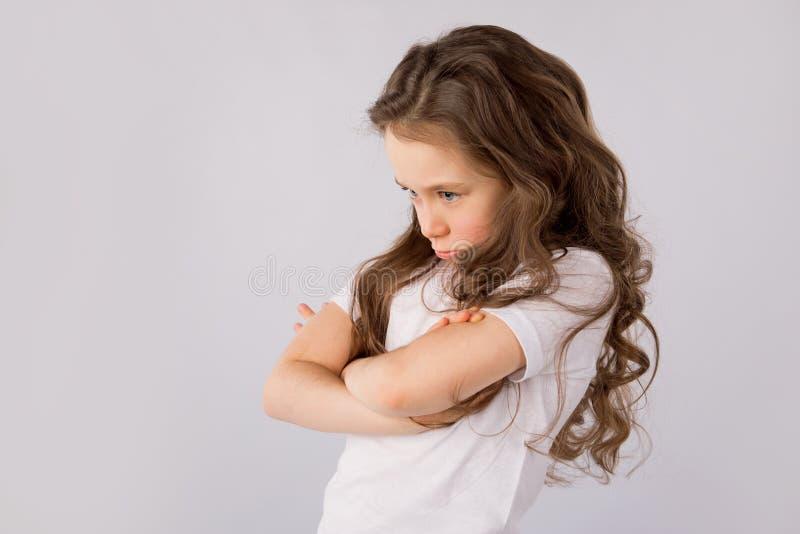 Portret van boos en droevig die meisje op witte achtergrond wordt geïsoleerd stock foto