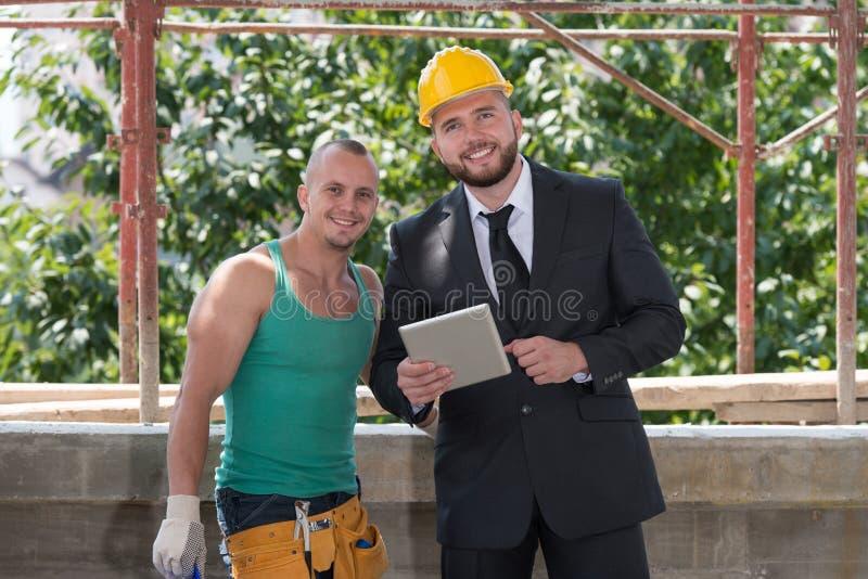 Portret van Bouwer And Businessman Working bij Bouw stock foto's
