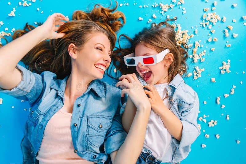 Portret van boven gelukkige tijd samen van mooie moeder die pret met dochter op blauwe vloer hebben Het leggen in popcorn stock foto