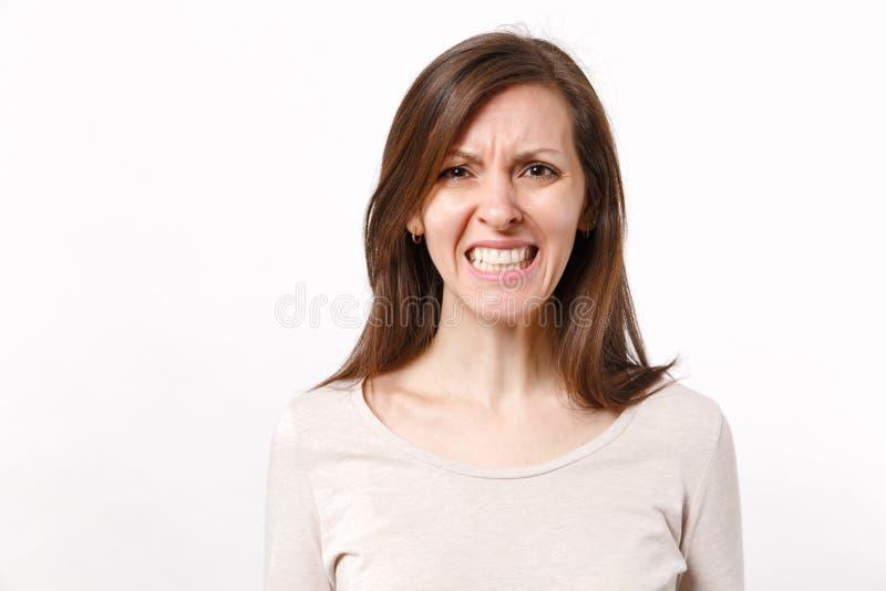 Portret van boze geïrriteerde ontevreden jonge vrouw met koppelingstanden in lichte die kleren op witte muur wordt geïsoleerd stock afbeelding
