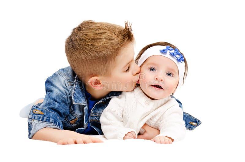 Portret van broer die zijn kleine leuke zuster kussen stock afbeeldingen