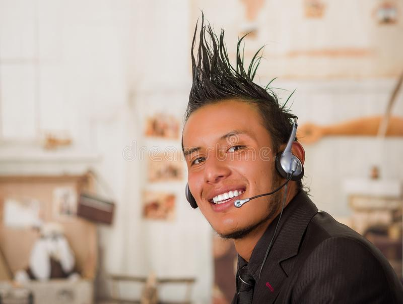 Portret van bureau punkarbeider die een kostuum met een kam dragen, die hoofdtelefoons in het werk, op een vage achtergrond met b royalty-vrije stock foto