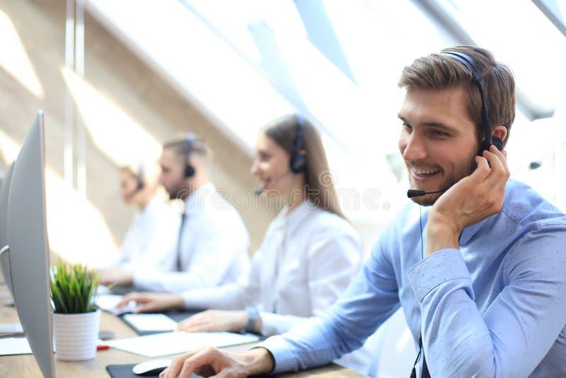 Portret van call centrearbeider die door zijn team wordt begeleid Glimlachende klantenondersteuningsexploitant op het werk royalty-vrije stock foto