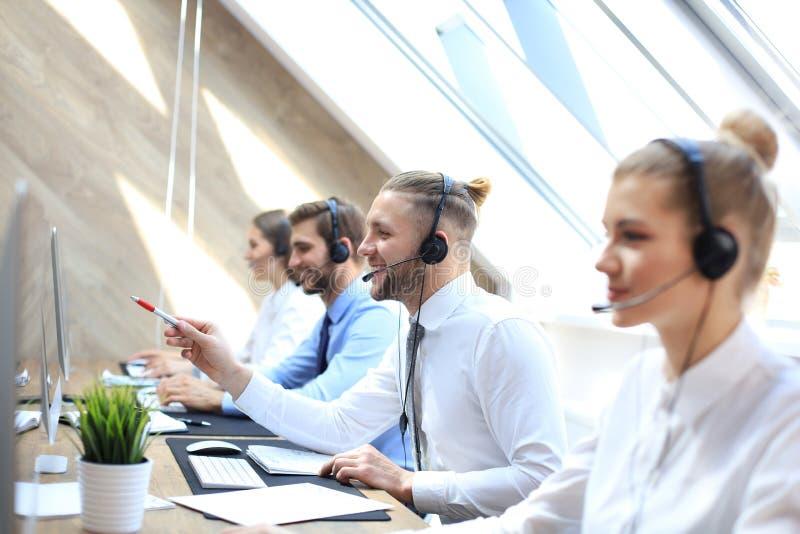 Portret van call centrearbeider die door zijn team wordt begeleid Glimlachende klantenondersteuningsexploitant op het werk stock fotografie