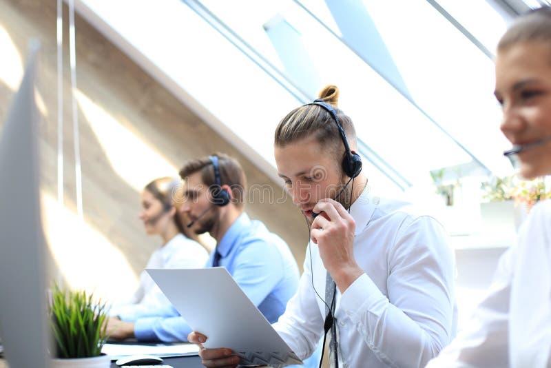 Portret van call centrearbeider die door zijn team wordt begeleid Glimlachende klantenondersteuningsexploitant op het werk stock afbeelding