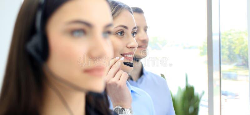 Portret van call centrearbeider door haar team wordt begeleid dat Glimlachende klantenondersteuningsexploitant op het werk royalty-vrije stock foto