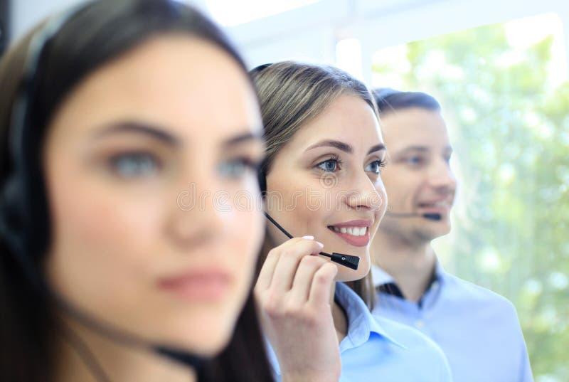 Portret van call centrearbeider door haar team wordt begeleid dat Glimlachende klantenondersteuningsexploitant op het werk royalty-vrije stock afbeelding