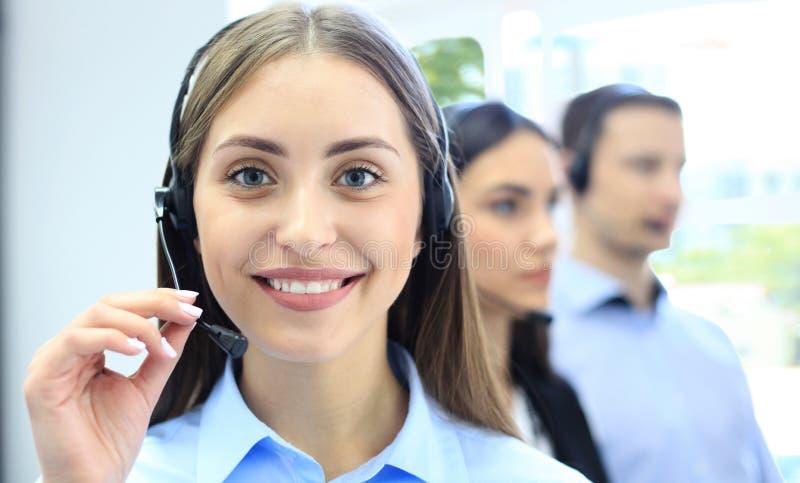 Portret van call centrearbeider door haar team wordt begeleid dat Glimlachende klantenondersteuningsexploitant op het werk stock fotografie