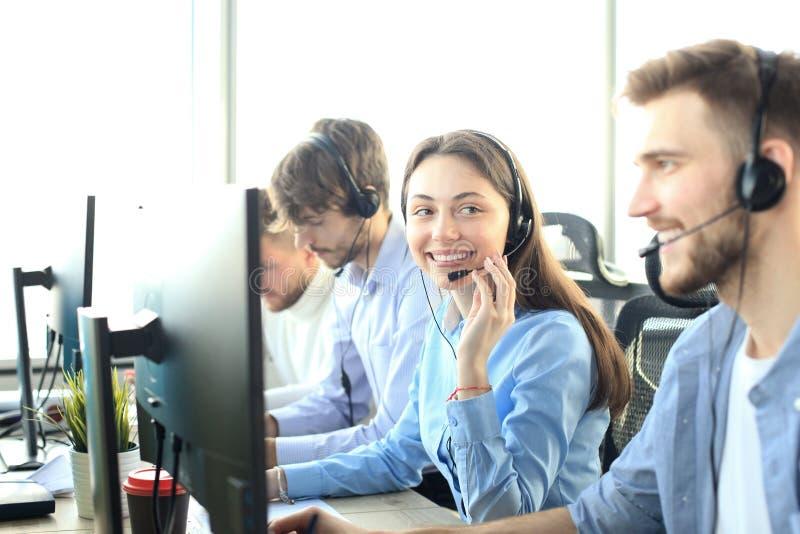 Portret van call centrearbeider door haar team wordt begeleid dat Glimlachende klantenondersteuningsexploitant op het werk royalty-vrije stock foto's