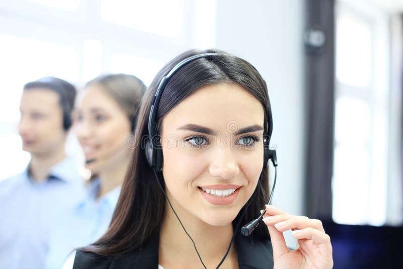 Portret van call centrearbeider door haar team wordt begeleid dat Glimlachende klantenondersteuningsexploitant op het werk royalty-vrije stock fotografie