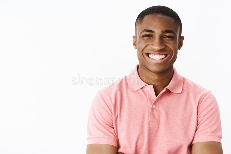 Portret van charismatisch prettig en gelukkig aantrekkelijk jong Afrikaans Amerikaans mannetje die in roze polo-overhemd, het gli stock afbeelding