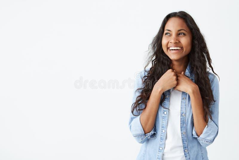 Portret van charismatische en charmante Afrikaans-Amerikaanse vrouw met lang golvend haar die modieus denimoverhemd, het glimlach royalty-vrije stock fotografie