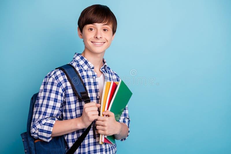 Portret van charmante de notaboeken die van de studentholding worden geïsoleerd dragend gecontroleerd overhemd kijken die over bl stock afbeeldingen