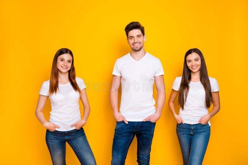 Portret van charmante mensen met lange haarglimlach die handen in zakken steken met een wit t-shirt denim jeans geïsoleerd stock afbeelding